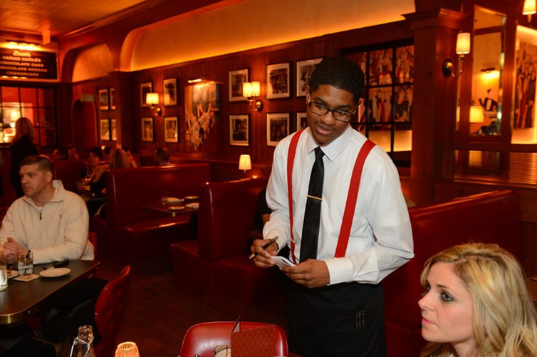 A friendly server talking with guests